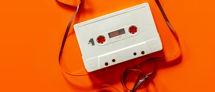 A white cassette tape, with its film pulled out and strung around it, lays atop a bright orange backdrop, invoking a feeling of energetic nostalgia