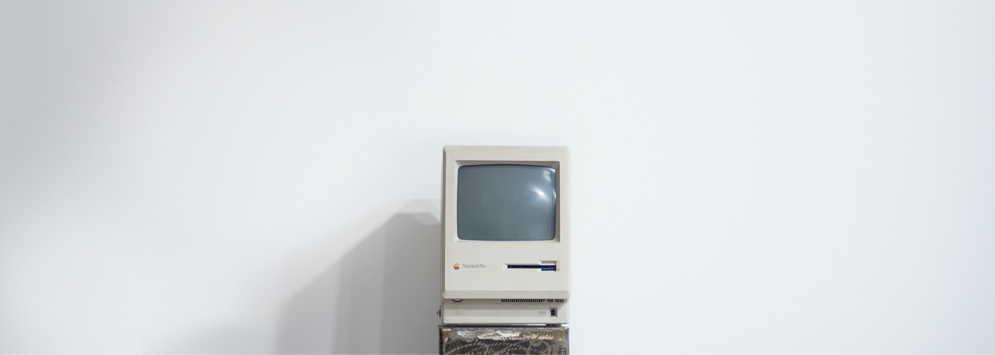 An old computer from the 1980s sites in front of a stark white background, like a scene from a museum.