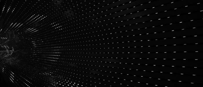 A dark tunnel illuminated by spots of white light, creating a star-like pattern Photo by o by Jared Arango on Unsplash